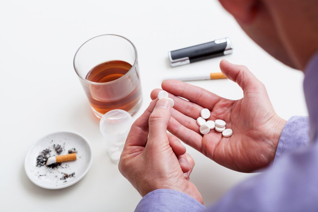 addiction treatment help - a handful of pills,